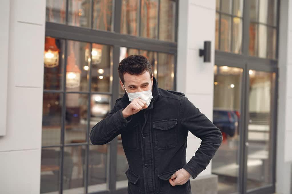 sick young man in medical mask walking on street during coronavirus pandemic